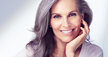 A gray-haired woman smiles to promote Mary Kay's dedication to celebrating natural beauty at every age.