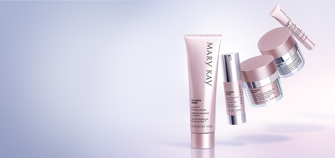 The five products that make up the Mary Kay TimeWise Repair Volu-Firm set, including a cleanser, a serum, a day cream, a night cream and an eye cream, hover in a crescent shape over a purple backdrop.