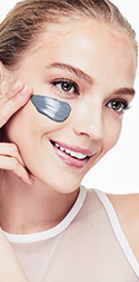 Model with a smear of Clear Proof Deep-Cleansing Charcoal Mask from Mary Kay on her cheek.