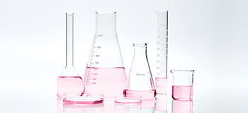 Scientific glass filled with pink liquid to represent Mary Kay research.