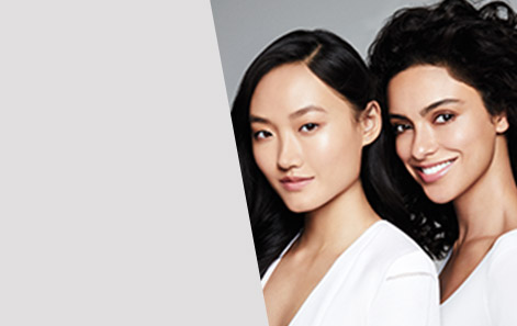 Two dark-haired women pose side-by-side in white tops.