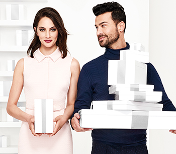Learn the many benefits of holiday shopping with your own Independent Beauty Consultant from Mary Kay. Image shows a woman holding a rectangle white gift box, a man stands next to her holding multiple white gift boxes.